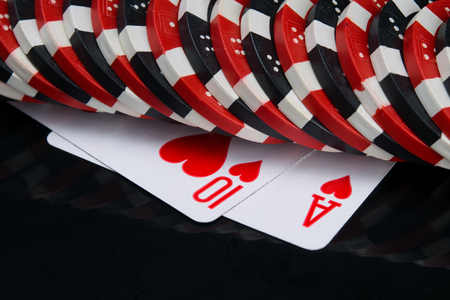 on a black background with a reflection on two cards, red suit, arranged in a row of game chips for poker Stock Photo