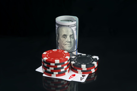 two stacks of colored chips, for playing in the casino, next to a roll of dollars, on a black background with a reflection of the cards, large denomination Stock Photo