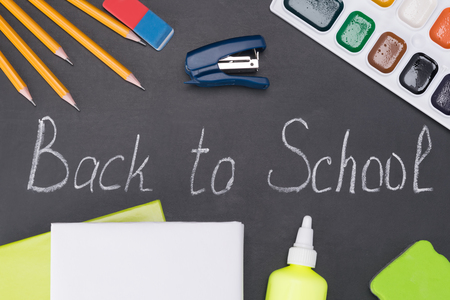 Items for childrens creativity are on a black chalkboard, which is written with chalk back to school