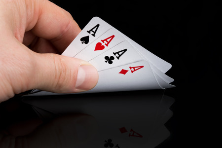 a poker player looks at his cards by raising them on a black table Stock Photo