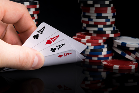 a poker player looks at his cards by raising them on a black table against the background of stacks of poker chips Stock Photo