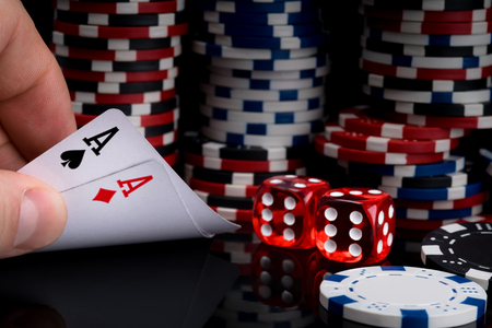 a poker player looks at his cards by raising them on a black table against the background of stacks of poker chips next to red dice