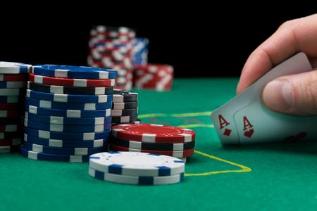un joueur de poker regarde ses cartes en les soulevant sur une table verte des jetons de poker sont dans la pile à côté d'eux Banque d'images
