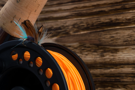 reel with orange fishing line and feather bait lie on a wooden background Stock Photo