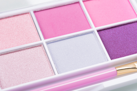 set of eyeshadow in pink colors with a brush on a light background, close-up