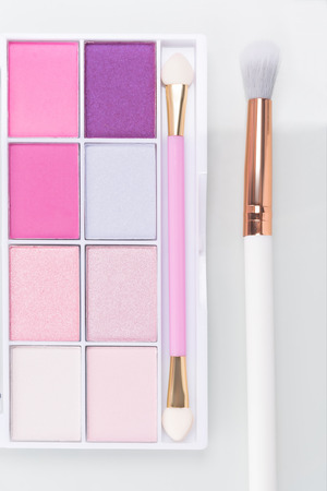 set of eyeshadow in pink colors with a brush on a light background Stock Photo