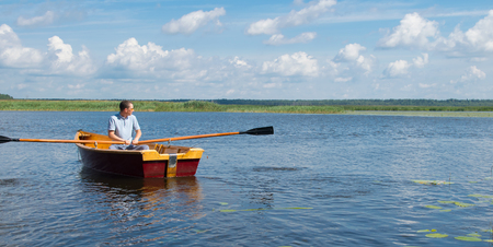 man resting on the lake, riding a boat with oars, there is a place for the inscription 版權商用圖片