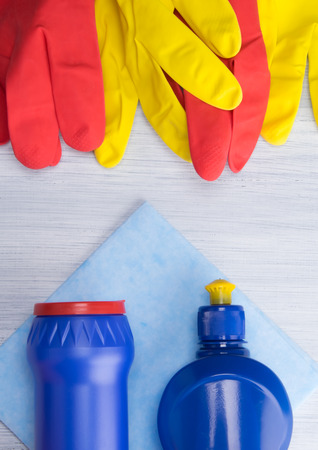 on a light background, with red and yellow gloves lying on top in a row, a rag and blue bottles with scouring powder and liquid are located at the bottom, for cleaning, close-up Stock Photo