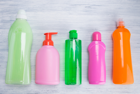 on a light background, multi-colored bottles with liquids for cleaning surfaces, washing dishes and washing clothes, arranged in a row