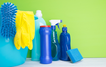 on a light gray and green background, multi-colored bottles with liquids and powder, a sponge, for cleaning surfaces, washing dishes and washing clothes, stands next to a blue bucket with a brush and yellow gloves, with space for an inscription Stock Photo