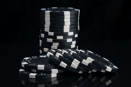 stack of black casino chips on a reflective surface
