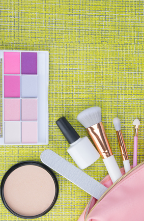 on a green background, with a place for an inscription, makeup brushes, a nail file, a set of powder for improving the complexion of the face, multi-colored eye shadow and nail polish lie in a pink cosmetic bag.