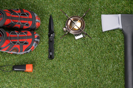on the green lawn are the items for the trip, comfortable shoes, a gas burner, an axe, a knife and a flashlight, there is a place for inscription