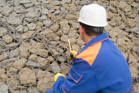 worker in blue uniform, measuring tape variety of stones used in the construction of the riverbed, close-up, rear view Stockfoto