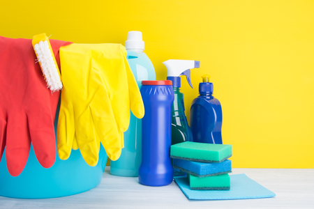 on a light gray and yellow background, multi-colored bottles with liquids and powder, sponges, for cleaning surfaces, washing dishes and washing clothes, next to it stands a blue bucket with brushes, yellow and red gloves, with space for an inscription