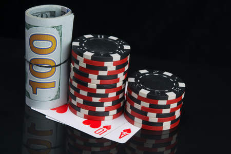 two stacks of colored chips, for playing in the casino, next to a roll of dollars, on a black background with cards