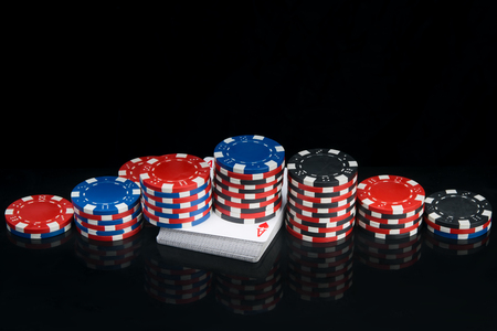a large long pyramid of casino chips on a black background of a table with a deck of cards