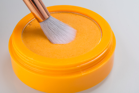 close-up of orange powder in a box for application to the hair, with a brush on a white background