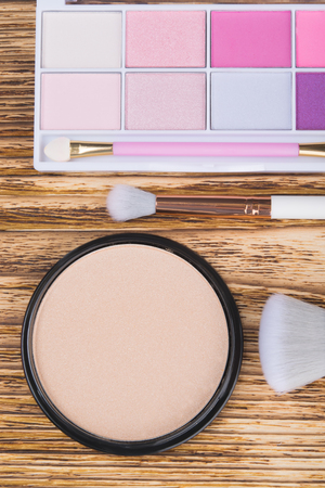 on a dark, wooden background, there is a powder for make-up, brushes and multi-colored eyeshadow