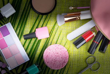 on a green background and a palm leaf, there are devices and tools for manicure and makeup, in a pink cosmetic bag, lipstick, nail polishes, multi-colored eye shadows, brushes and powder for improving complexion