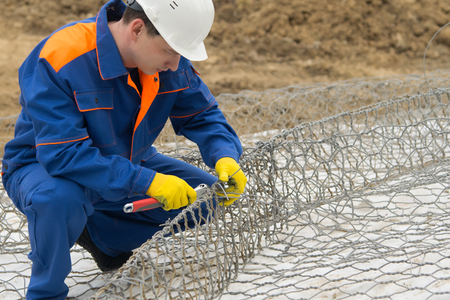 working in a blue uniform, knit mesh for cells under the stones to improve the shore, close-up Stock Photo