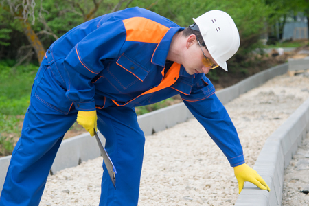 master in blue uniform, takes the amount of work done to install curbs in the Park, in the construction of the road