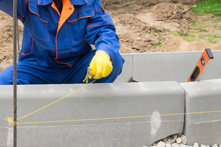 master in blue form sets the control thread, for smooth laying of curbstone, close-up