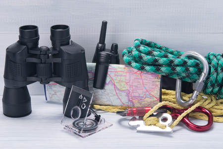 on a light background, travel kit, binoculars, compass, rope, carabiner, walkie-talkie and map Stock Photo