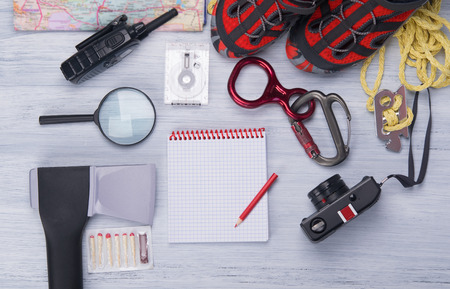 on a light background, a set for the traveler, ax, compass, rope, carabiner, magnifying glass, comfortable shoes, walkie-talkie, matches, camera ,map and notebook with pencil for records Stock Photo
