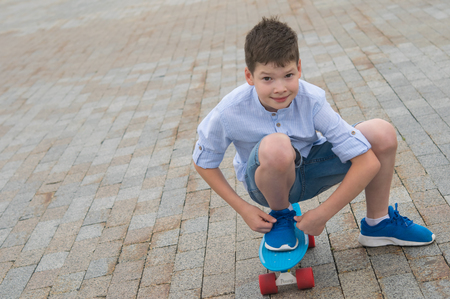 cheerful boy, riding on a stone block on a skateboard, putting one foot on it