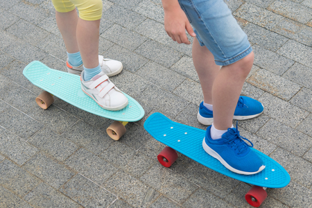 against the stone paving, close-up, two skateboards with the feet of a boy and a girl on them Stock Photo