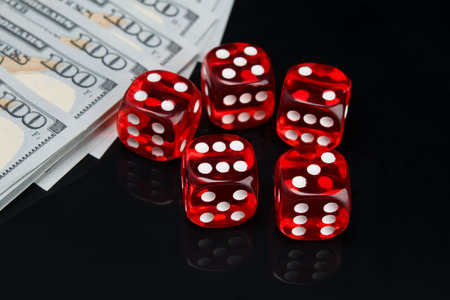 on a black background with a reflection, five red dice for the game and hundred dollar bills laid out in a row