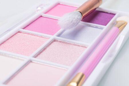 Paleta de sombras de maquillaje brillantes con un pincel, fondo de cerca