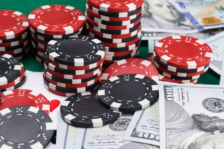 a lot of poker chips and money are on the green table, close-up, background