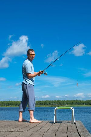a man in yellow glasses on the pier, throws a fishing rod for fishing, against the blue sky and the lake