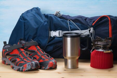 against the background of a tourist backpack, gas burner and travel shoes, on a wooden table Foto de archivo