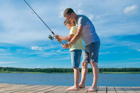 father shows his son on the pier how to hold a fishing rod to catch fish, against the blue lake and sky 版權商用圖片 - 125432975