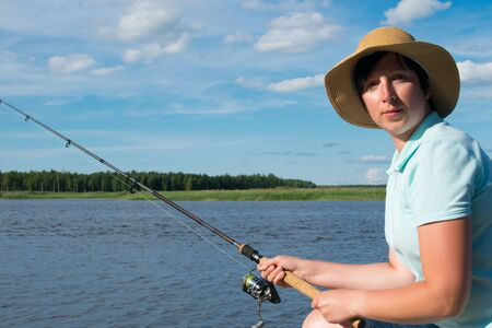 close-up, a woman with a hat, against a background of a lake, holds a fishing pole to catch a fish