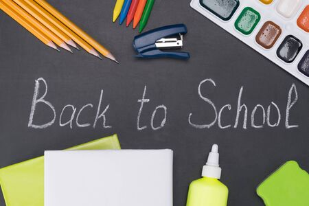 set of school supplies on the background of a chalk board with the inscription