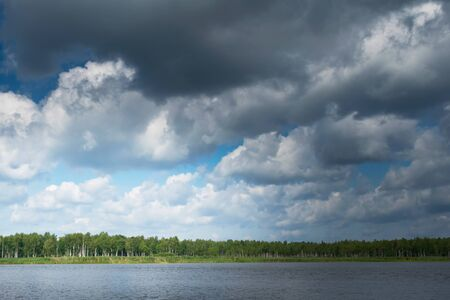 background of white clouds in the blue sky over a lake in the forest
