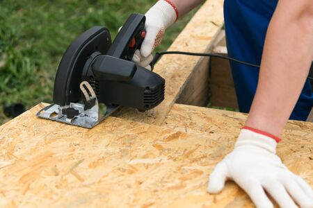 man cuts a piece of plywood with a saw, close-up