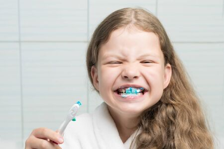 a girl in a white bathrobe brushed her teeth with blue toothpaste in the bathroom