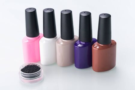 multi-colored nail polishes are in a row on a light background Standard-Bild