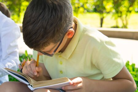 close-up, in the park, in the fresh air, a schoolboy enthusiastically does a task on arithmetic