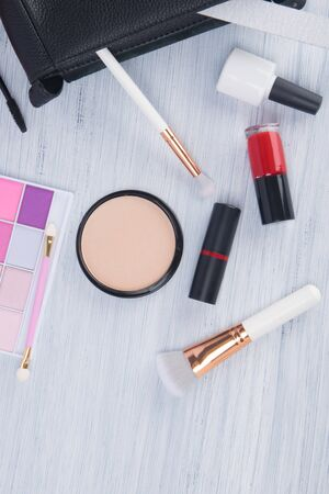 on a light background scattered items for makeup and manicure, multi-colored eye shadow, face powder with brushes, nail polishes and lipstick Imagens
