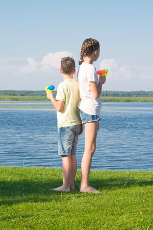 boy and girl on the lake, holding water pistols and stand with their backs to each other, against a beautiful landscape, looking at the water
