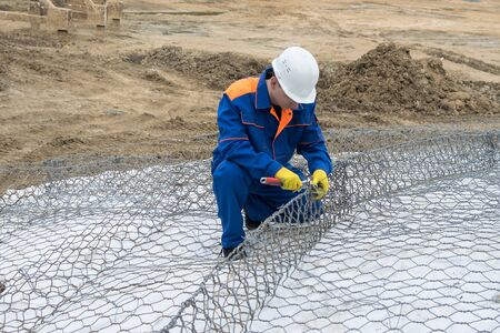 worker at a construction site in a white helmet makes a construction of iron wire, side view Archivio Fotografico