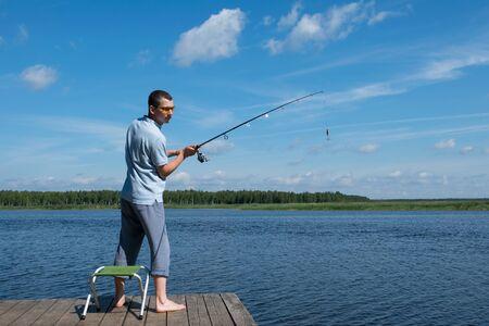 L'homme à lunettes de soleil jette un appât sur une filature dans le lac pour la pêche
