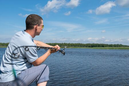 man in sunglasses throws spinning into the lake for fishing, close-up