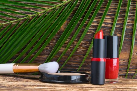 against the background of a dark wooden table and a green palm leaf, close-up, red nail Polish, lipstick and powder to align the face with a white brush Reklamní fotografie